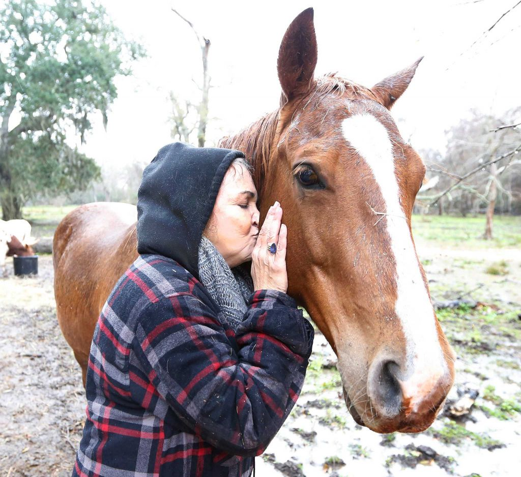 Rowdy Girl Sanctuary resident Cami receives a kiss from ranch owner Renee King-Sonnen.